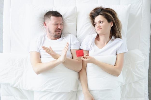Junger mann weigert sich, kondome zu verwenden, während er mit einer frau im bett liegt, männliche verhütungsmethoden