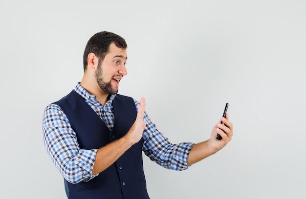 Junger mann winkt hand auf video-chat in hemd, weste und schaut froh.