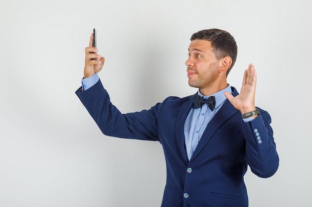 Junger mann winkt hand auf videoanruf im anzug und sieht fröhlich aus.