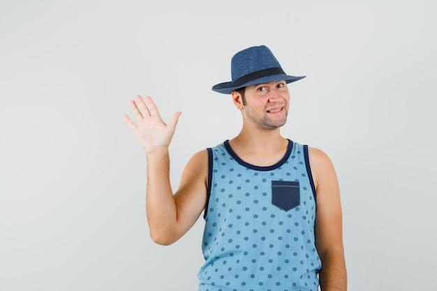 Junger mann winkt hand für gruß in blauem unterhemd, hut und schaut fröhlich. vorderansicht.