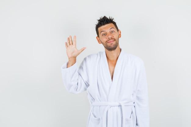 Junger mann winkt hand zum begrüßen im weißen bademantel und schaut fröhlich. vorderansicht.