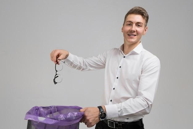 Junger mann wirft gläser in den abfall, der auf weißem hintergrund lokalisiert wird