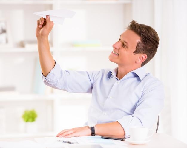 Junger mann wirft papierflugzeug und lächeln.