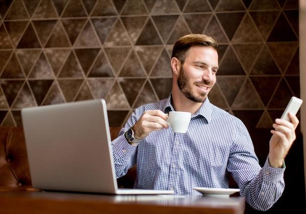 Junger mann workin auf laptop im café