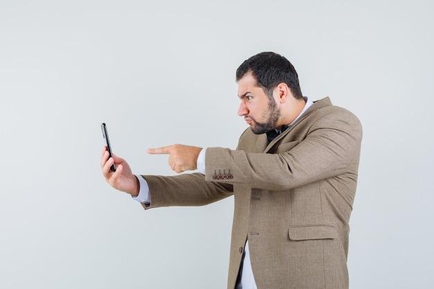 Junger mann zeigt auf bildschirm auf video-chat im anzug und schaut wütend, vorderansicht.