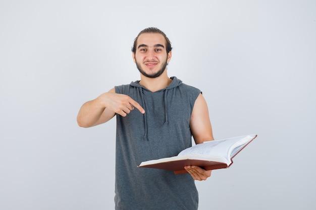 Junger mann zeigt auf buch im ärmellosen kapuzenpulli und sieht hübsch aus, vorderansicht.