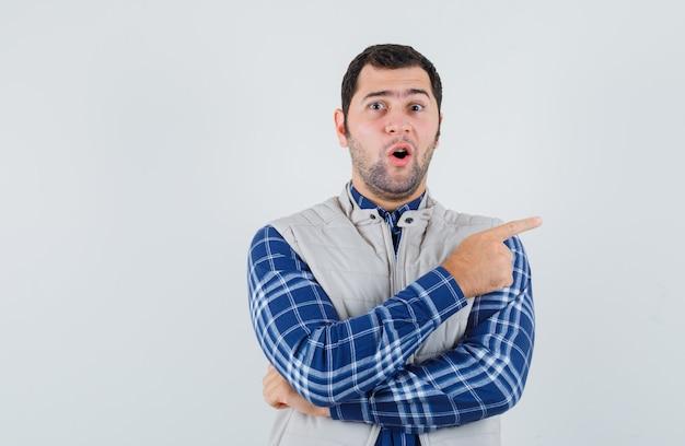 Junger mann zeigt auf die linke seite in hemd, ärmelloser jacke und sieht überrascht aus. vorderansicht.