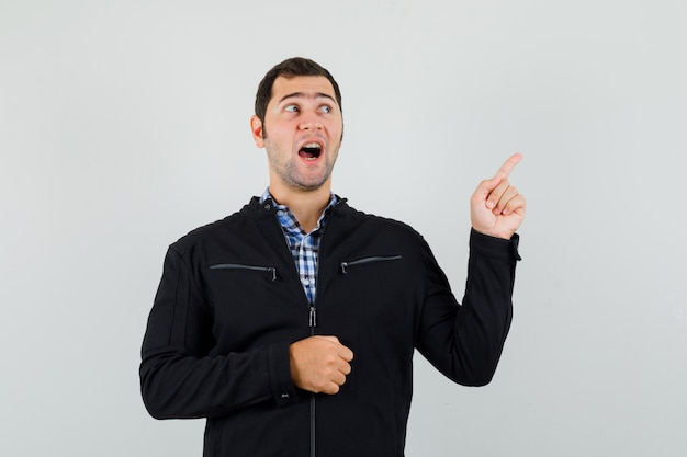 Junger mann zeigt auf die obere rechte ecke in hemd, jacke und schaut hoffnungsvoll, vorderansicht.