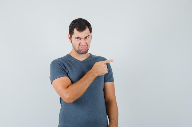 Junger mann zeigt auf die rechte seite im grauen t-shirt und sieht wütend aus