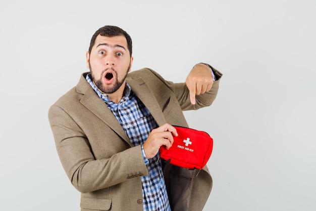 Junger mann zeigt auf erste-hilfe-kasten in hemd, jacke und schaut schockiert.