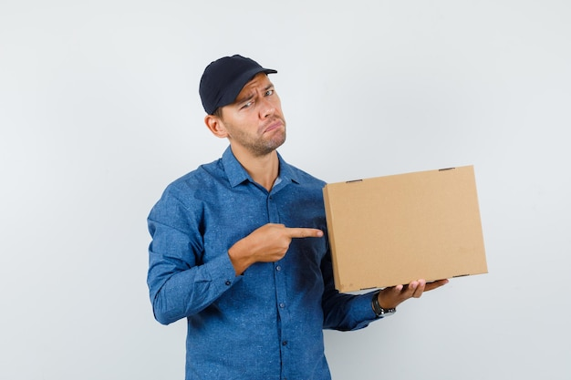 Junger mann zeigt auf karton in blauem hemd, mütze und sieht verzweifelt aus. vorderansicht.