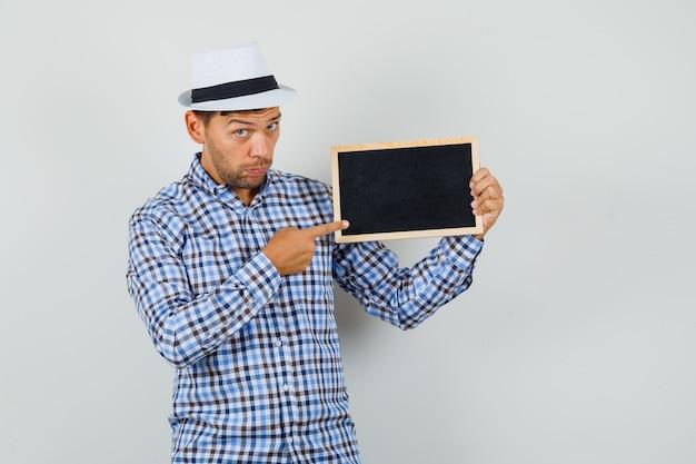Junger mann zeigt auf leeren rahmen im karierten hemd
