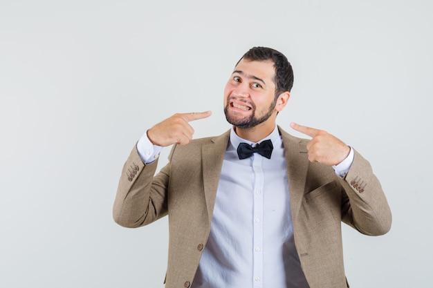 Junger mann zeigt auf sein lächeln im anzug und schaut geliebt, vorderansicht.