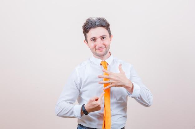 Junger mann zeigt auf seine fünf finger in hemd, jeans und sieht fröhlich aus