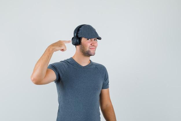 Junger mann zeigt auf seine kopfhörer in t-shirt, mütze und sieht fröhlich aus. vorderansicht.