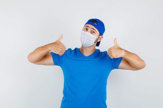 Junger mann zeigt daumen hoch in blauem t-shirt und mütze, maske und sieht erfreut aus