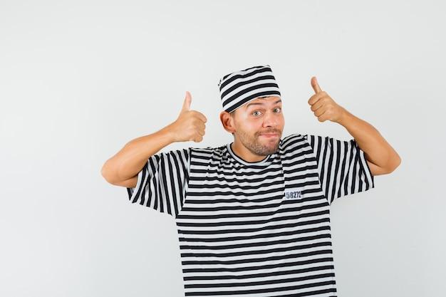 Junger mann zeigt daumen hoch in gestreiftem t-shirt, hut und sieht fröhlich aus.