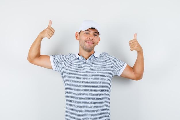 Junger mann zeigt daumen hoch in t-shirt und mütze und sieht fröhlich aus