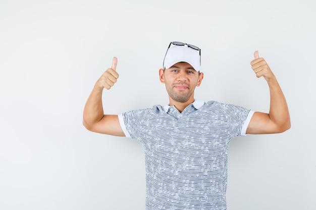 Junger mann zeigt daumen hoch in t-shirt und mütze und sieht zufrieden aus