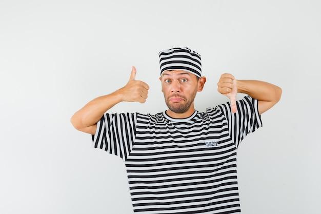 Junger mann zeigt daumen hoch und runter in gestreiftem t-shirt, hut und zögernd.