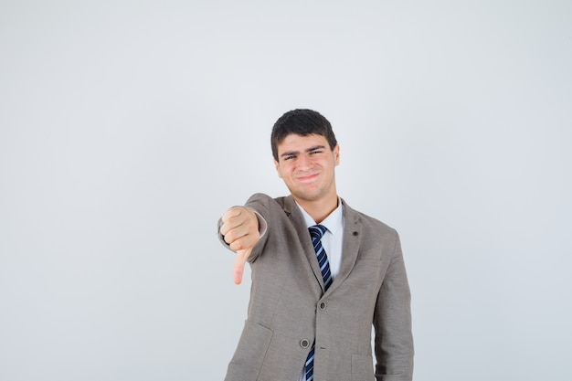 Junger mann zeigt daumen nach unten im anzug