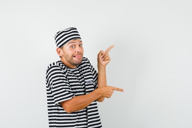 Junger mann zeigt finger auf und ab in gestreiftem t-shirt hut und sieht munter aus