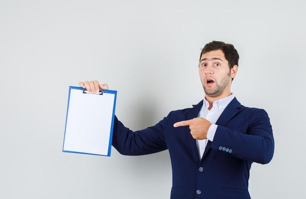 Junger mann zeigt finger auf zwischenablage im anzug und schaut erstaunt, vorderansicht.