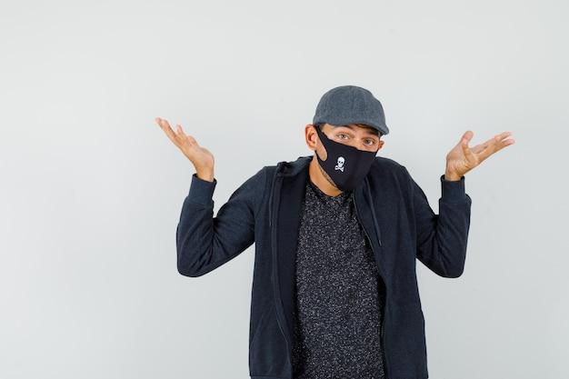 Junger mann zeigt hilflose geste durch achselzucken in t-shirt, jacke, mütze, maske