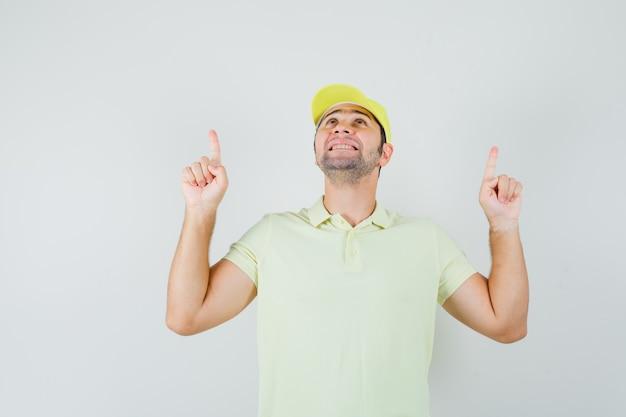 Junger mann zeigt in gelber uniform und sieht dankbar aus.