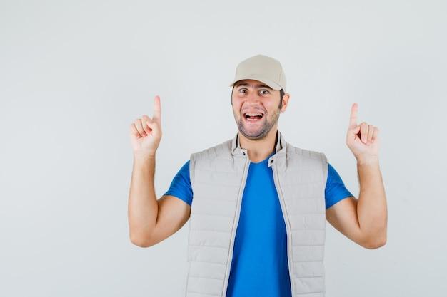 Junger mann zeigt in t-shirt, jacke, mütze und sieht fröhlich aus, vorderansicht.