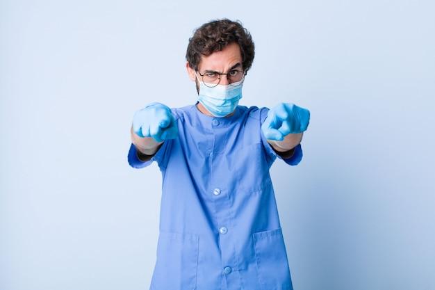Junger mann zeigt mit beiden fingern und wütendem gesichtsausdruck nach vorne in die kamera und fordert sie auf, ihre pflicht zu erfüllen. coronavirus-konzept