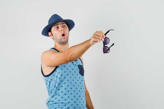 Junger mann zeigt mit brille im blauen unterhemd, hut weg und sieht überrascht aus. vorderansicht.