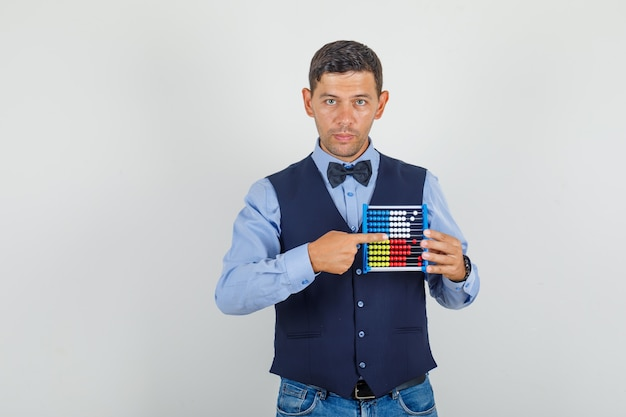 Junger mann zeigt mit dem finger auf abakus im anzug, jeans und sieht ernst aus.