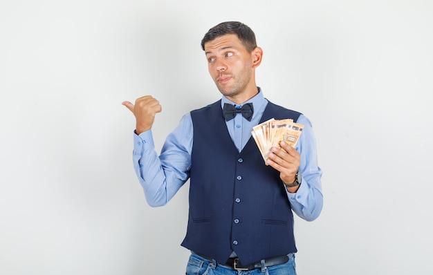 Junger mann zeigt mit geld im anzug, jeans weg