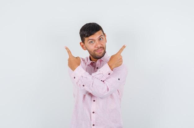 Junger mann zeigt nach oben und lächelt in rosa hemd, vorderansicht.