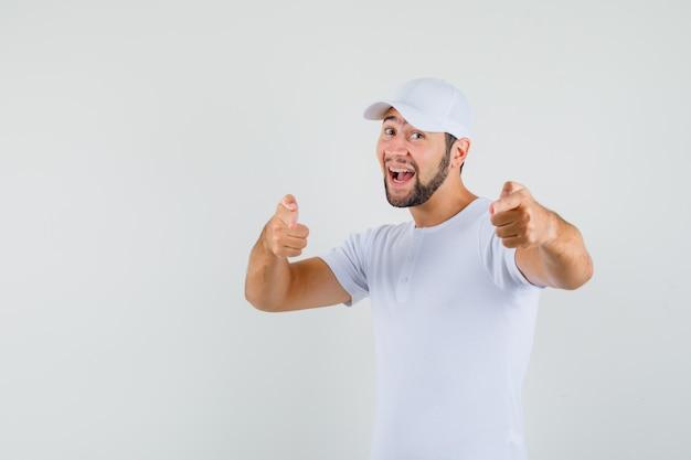Junger mann zeigt nach vorne in t-shirt und schaut fröhlich. vorderansicht.
