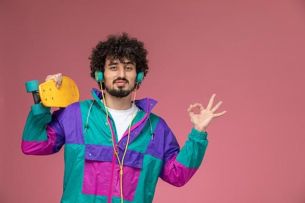 Junger mann zeigt ok geste mit gelbem scate board