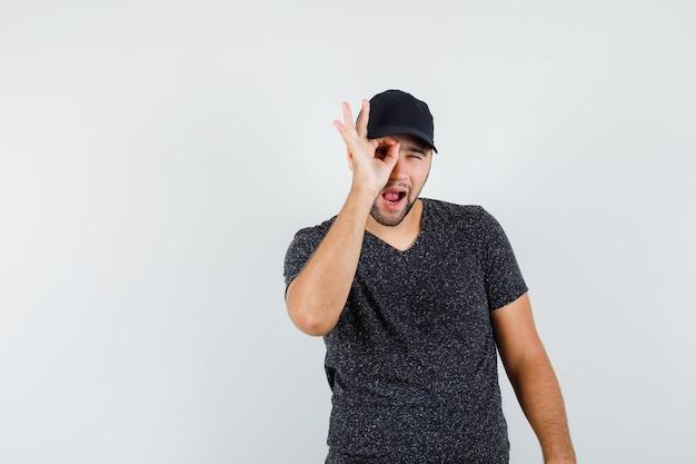 Junger mann zeigt ok geste und zwinkert auge in t-shirt und mütze