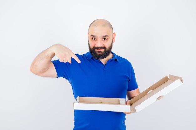 Junger mann zeigt pizzakarton im t-shirt und sieht glücklich aus, vorderansicht.