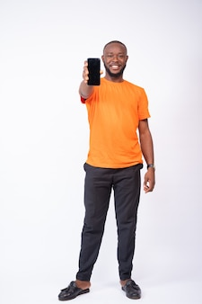 Junger mann zeigt seinen telefonbildschirm isoliert auf weißem hintergrund