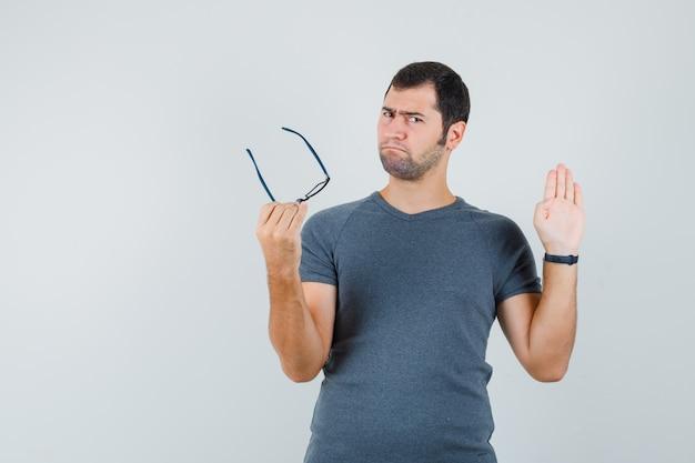 Junger mann zeigt stoppgeste, hält brille im grauen t-shirt, vorderansicht.