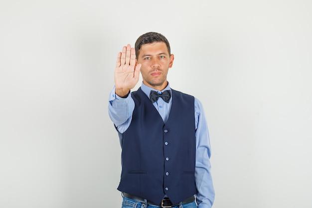 Junger mann zeigt stoppgeste in anzug, jeans und selbstbewusst aussehend