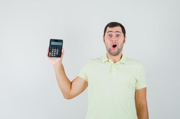 Junger mann zeigt taschenrechner im t-shirt und schaut erstaunt, vorderansicht.