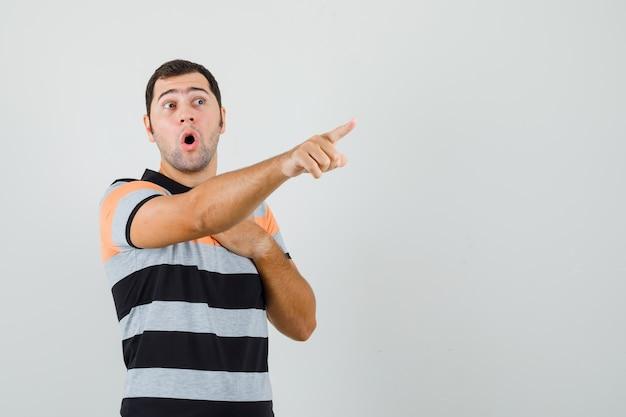 Junger mann zeigt weg, während er hand auf seiner brust im t-shirt hält und überrascht aussieht. vorderansicht. freier speicherplatz für ihren text