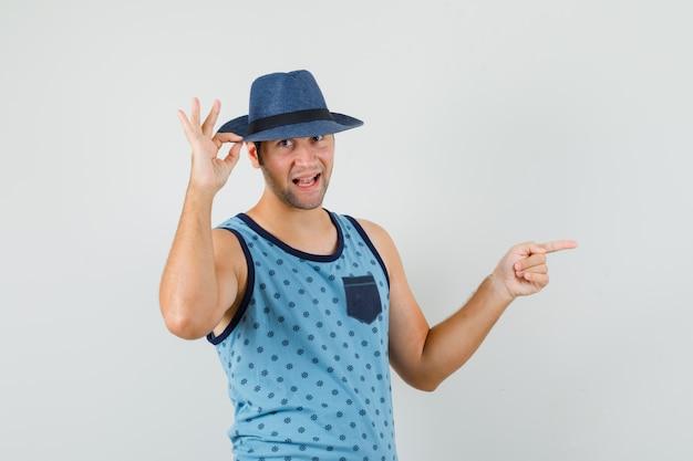 Junger mann zeigt zur seite, hält hut im blauen unterhemd, hut und sieht fröhlich aus. vorderansicht.