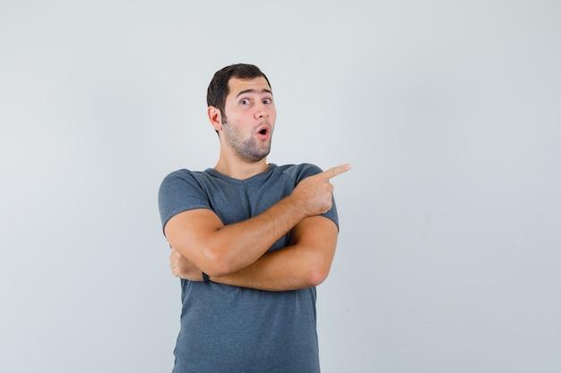 Junger mann zeigt zur seite im grauen t-shirt und sieht überrascht aus. vorderansicht.