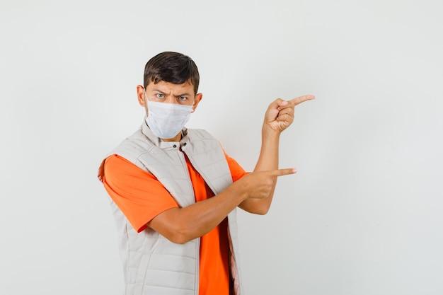 Junger mann zeigt zur seite in t-shirt, jacke, maske und sieht ernst aus.