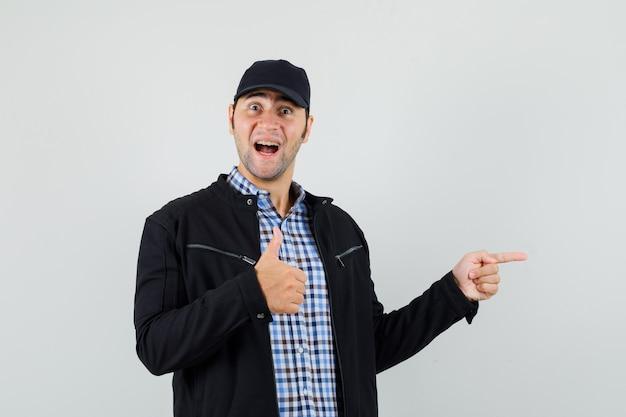Junger mann zeigt zur seite, zeigt daumen oben in hemd, jacke, mütze und sieht fröhlich aus. vorderansicht.