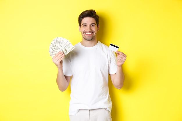 Junger mann zieht geld von kreditkarte ab, lächelt erfreut und steht über gelbem hintergrund.