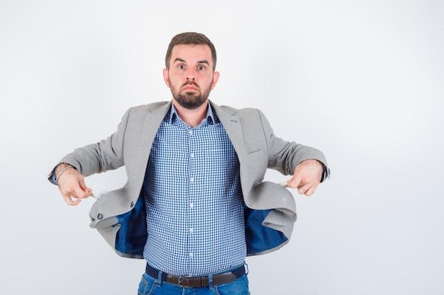 Junger mann zieht jackentaschen in hemd, jeans, anzugjacke heraus und sieht ernst aus. vorderansicht.